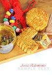 Asia tea time elements. Flower tea, moon cake, lucky knot, sandalwood fan on a wooden board Royalty Free Stock Photo