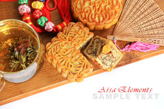 Asia tea time elements. Flower tea, moon cake, lucky knot, sandalwood fan on a wooden board Royalty Free Stock Images