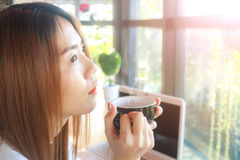 Hold coffee and think. Asia teenage hold coffee and think in cafe. Soft flare filter royalty free stock images