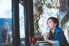 Asia teenage sitting alone in happiness with drinking in cafe. Royalty Free Stock Image