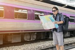 Asia tourist looking a map for travel by the train. Traveler concept stock photos