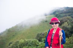 Asia trekker woman in red. Asian trekker woman in red hat, red jacket holding walking stick in national park with mountain view background. A woman smile with Royalty Free Stock Photos