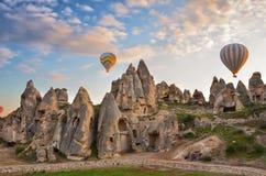 ASIA, TURKEY,  CAPPADOCIA. Hot air balloons flying over spectacular Cappadocia, Turkey. Sunset Stock Photo
