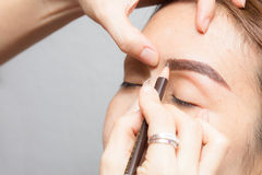 Asia woman applying permanent make up eyebrows tattoo. Stock Photos