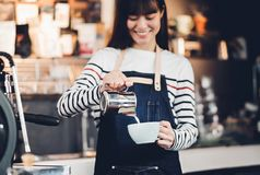 Asia woman barista pour milk into hot coffee cup at counter bar Royalty Free Stock Photography
