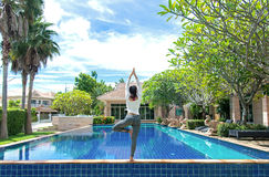 Asia woman doing yoga fitness exercise for relax and healthy beside swimming pool background. Royalty Free Stock Images