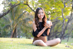 Asia woman drinking coffee in park Stock Image