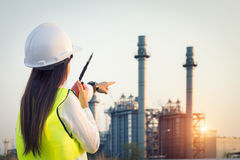 Asia woman Engineer working. In a power plant with talking on the walkie-talkie for controlling work royalty free stock photo