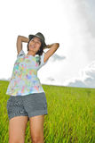 Asia woman  in the grassland. Woman picture stands in green grass in daytime Royalty Free Stock Image