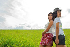 Asia woman  in the grassland. Woman picture stands in green grass in daytime Stock Images