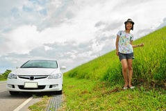 Asia woman  in the grassland. Woman picture stands in green grass in daytime Royalty Free Stock Images