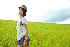 Asia woman  in the grassland. Woman picture stands in green grass in daytime Stock Photos