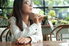 Asia woman holding mobile phone sitting and waiting for someone. Young asia woman holding mobile phone sitting and waiting for someone in coffee cafe. image for Royalty Free Stock Photography