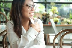 Asia woman holding mobile phone sitting and waiting for someone. Young asia woman holding mobile phone sitting and waiting for someone in coffee cafe. image for Royalty Free Stock Images