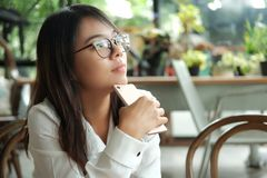 Asia woman holding mobile phone sitting and waiting for someone. Young asia woman holding mobile phone sitting and waiting for someone in coffee cafe. image for Stock Images