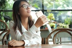 Asia woman holding mobile phone sitting and waiting for someone. Young asia woman holding mobile phone sitting and waiting for someone in coffee cafe. image for Stock Photography
