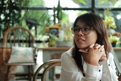 Asia woman holding mobile phone sitting and waiting for someone. Young asia woman holding mobile phone sitting and waiting for someone in coffee cafe. image for Stock Photos