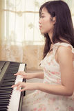 Asia woman playing the piano Royalty Free Stock Image