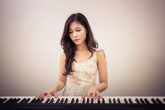 Asia woman playing the piano Stock Images