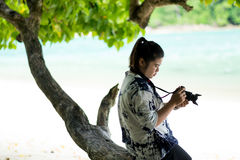 Asia woman sitting on timber under tree and using camera for tak Royalty Free Stock Photos