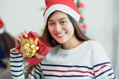 Asia woman smile holding gold xmas gift box at holiday party with decoration flag at background,present giving Christmas party royalty free stock photography