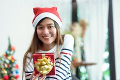 Asia woman smile holding gold xmas gift box at holiday party wit stock images