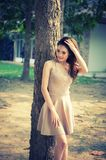 Asia woman standing lying tree in park on sun stock images