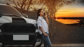An Asia woman standing next to the car alone and using mobile phone. Wait for someone with beautiful nature background Stock Images