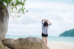 Asia woman standing on sand beach and putting hand on head herse. Young asia woman standing on sand beach and putting hand on head herself. have big rock placed Royalty Free Stock Image
