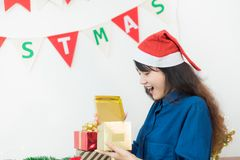 Asia woman surprise when open gold xmas gift box at holiday part. Y with decoration flag at background,giving Christmas party present,wow feeling and  happiness Stock Photography