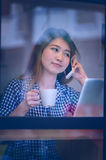 Asia woman talking  phone in cafe and enjoying coffee Stock Images