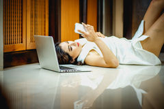 Asia woman using smart phone and laptop lying on floor. Asia woman using smart phone and laptop lying on the floor at home Stock Image