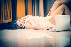 Asia woman using smart phone and laptop lying on floor Royalty Free Stock Images