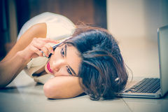 Asia woman using smart phone and laptop lying on floor Stock Photography