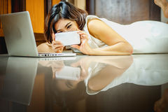 Asia woman using smart phone and laptop lying on floor. Asia woman using smart phone and laptop lying on the floor at home Stock Photos