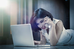 Asia woman using smart phone and laptop lying on floor. Asia woman using smart phone and laptop lying on the floor at home, add flare, vintage style Stock Photography