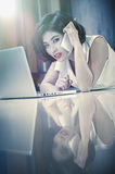 Asia woman using smart phone and laptop lying on floor. Asia woman using smart phone and laptop lying on the floor at home, add flare, vintage style Royalty Free Stock Images
