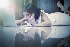 Asia woman using smart phone and laptop lying on floor. Asia woman using smart phone and laptop lying on the floor at home, add flare, vintage style Royalty Free Stock Photos
