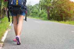 The asia woman walking on the road in asia. Asian girl backpack in the road and forest background Royalty Free Stock Photo