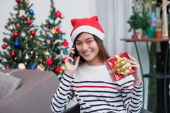 Asia woman wear santa hat and holding gift box and use mobile talk with friend and sitting on sofa in christmas party,holiday royalty free stock photos