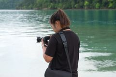 Asia woman wearing black shirt standing on beach and using camer. Young asia woman wearing black shirt standing on beach and using camera for take photo. have Stock Photos