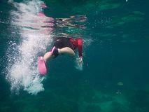 Asia woman wearing red shirt and dive goggle. she diving snorkel. Young asia woman wearing red shirt and dive goggle. she diving snorkeling under sea. this image royalty free stock image