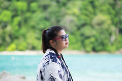Asia woman wearing sunglasses looking scenery view. sea and gree Stock Image