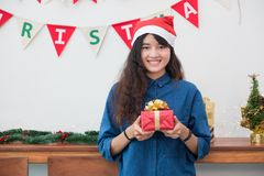 Asia woman in xmas party gift giving gold box to friend with smi Stock Image