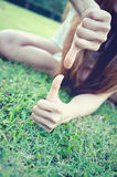 Asia women lying with Hand showing thumb up and down Stock Photos