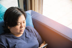 Asia women 40s holding smartphone thinking on sofa. Asian woman 40s white skin and plump body in blue dress holding smartphone have a doubt and think gesture on Stock Image
