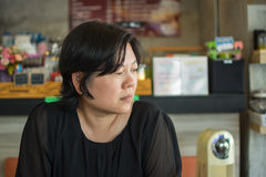 Asia women think in coffee shop. Asia woman 40s white skin in black dress have a doubt and think gesture in a coffee shop cafe Stock Image