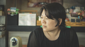 Asia women think in coffee shop. Asia woman 40s white skin in black dress have a doubt and think gesture in a coffee shop cafe Royalty Free Stock Photo