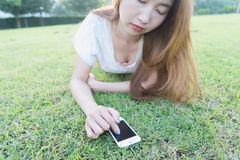 Asia women write text messaging on her phone lying on grass Royalty Free Stock Photos