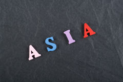 ASIA word on black board background composed from colorful abc alphabet block wooden letters, copy space for ad text. Learning english concept royalty free illustration